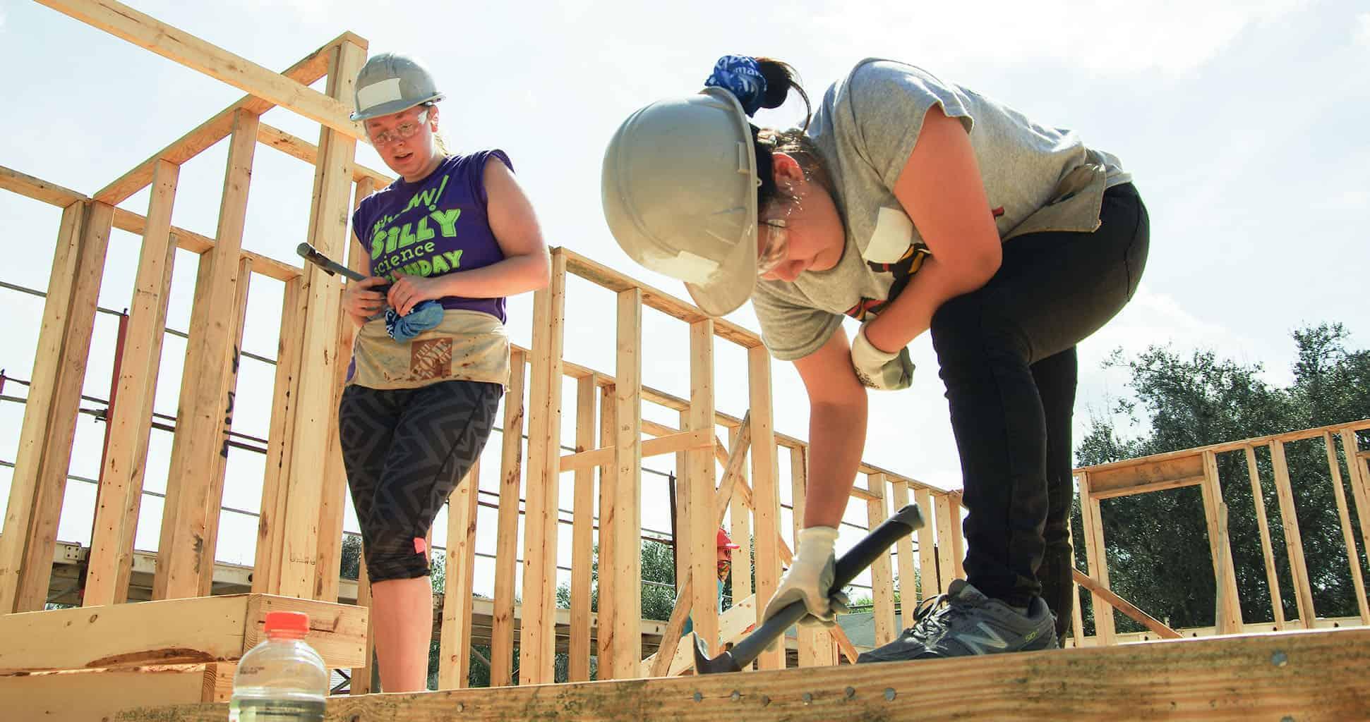 Two women in hard hats build walls