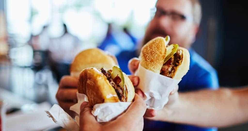 Three burgers in hands