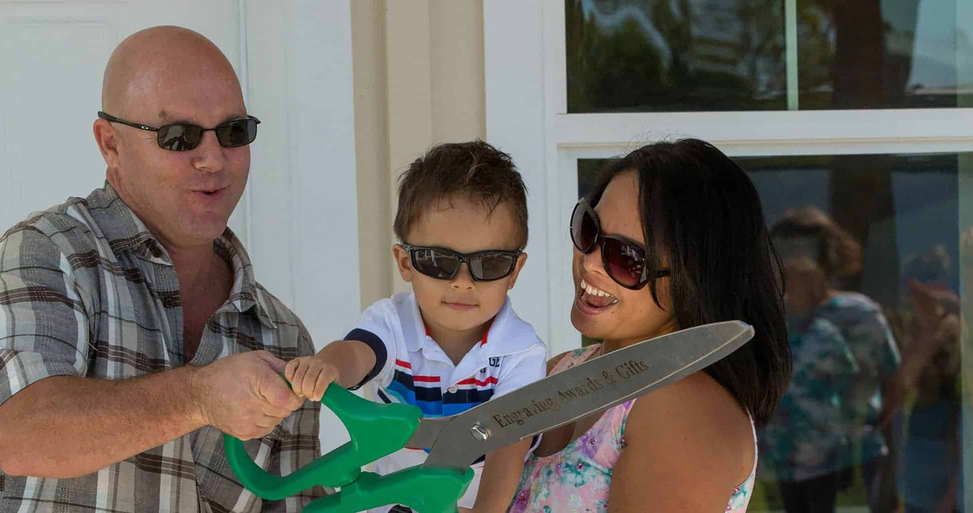Mother Father and Child holding large scissors