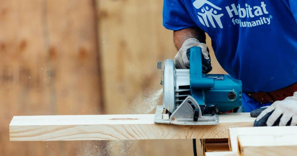 A staff member saws lumber