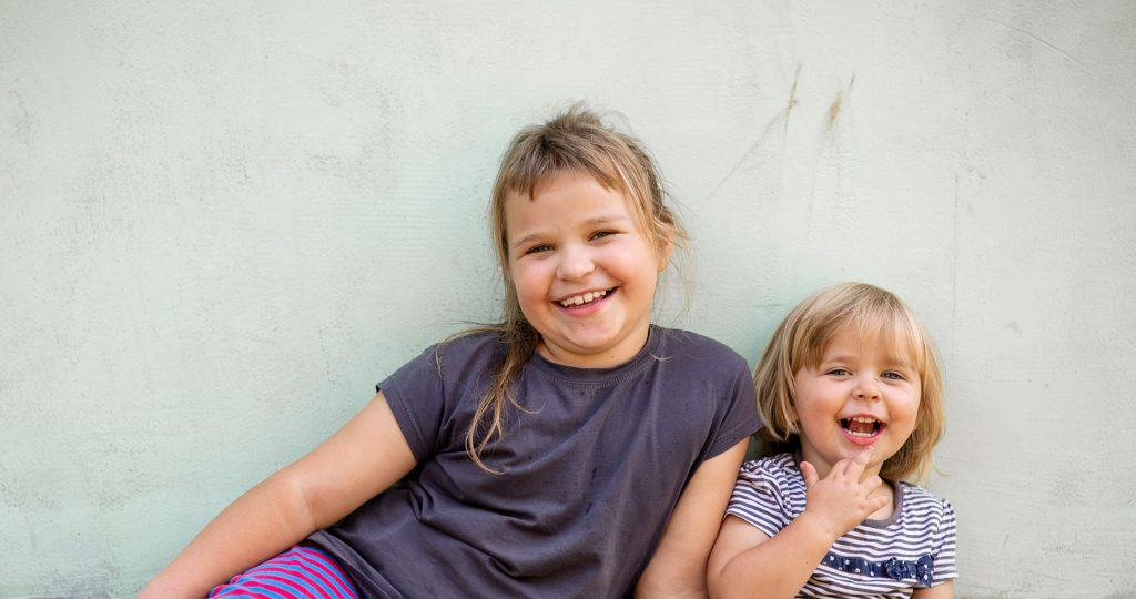 Weronika Kawka, 7, and her sister Amelka Kawka, 2, in front of one of the walls of the home being built for them by volunteers with Habitat for Humanity