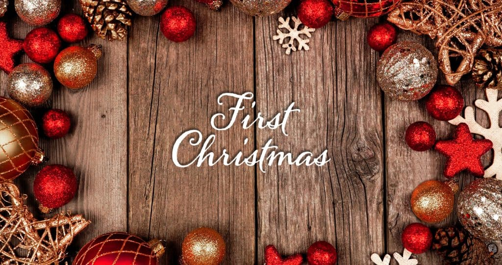 First Christmas written on wood surrounded by red and gold ornaments