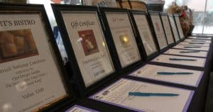 Row of framed certificate with bid sheets and pens