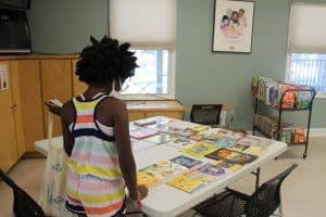 A young girls looks at a table full of books
