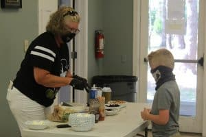 A volunteer serves a sundae to a young boy
