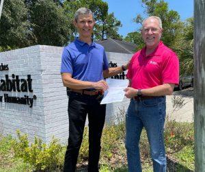 A member of Ponte Vedra Beach Rotary hands a check to Beaches Habitat CEO