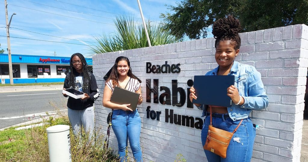 3 young women holding laptops in front of Beaches Habitat sign