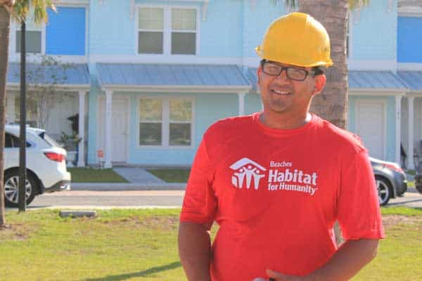 Man wearing hard hat standing in front of blue townhomes