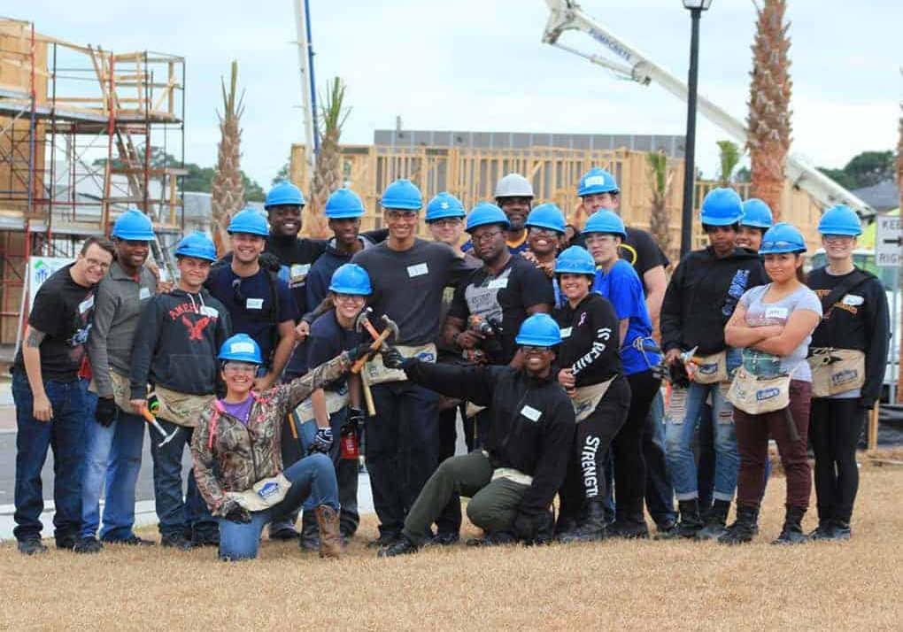 A volunteer group in blue hard hats after building