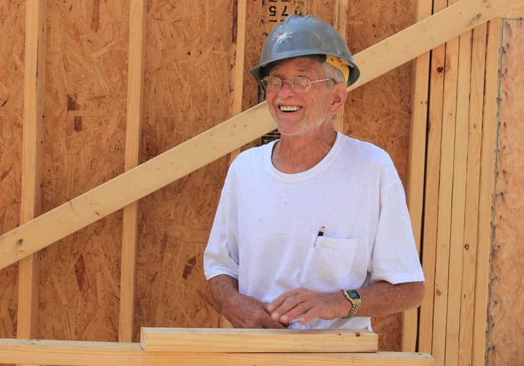 A smiling volunteer with building material